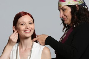 makeup artist adjusting model