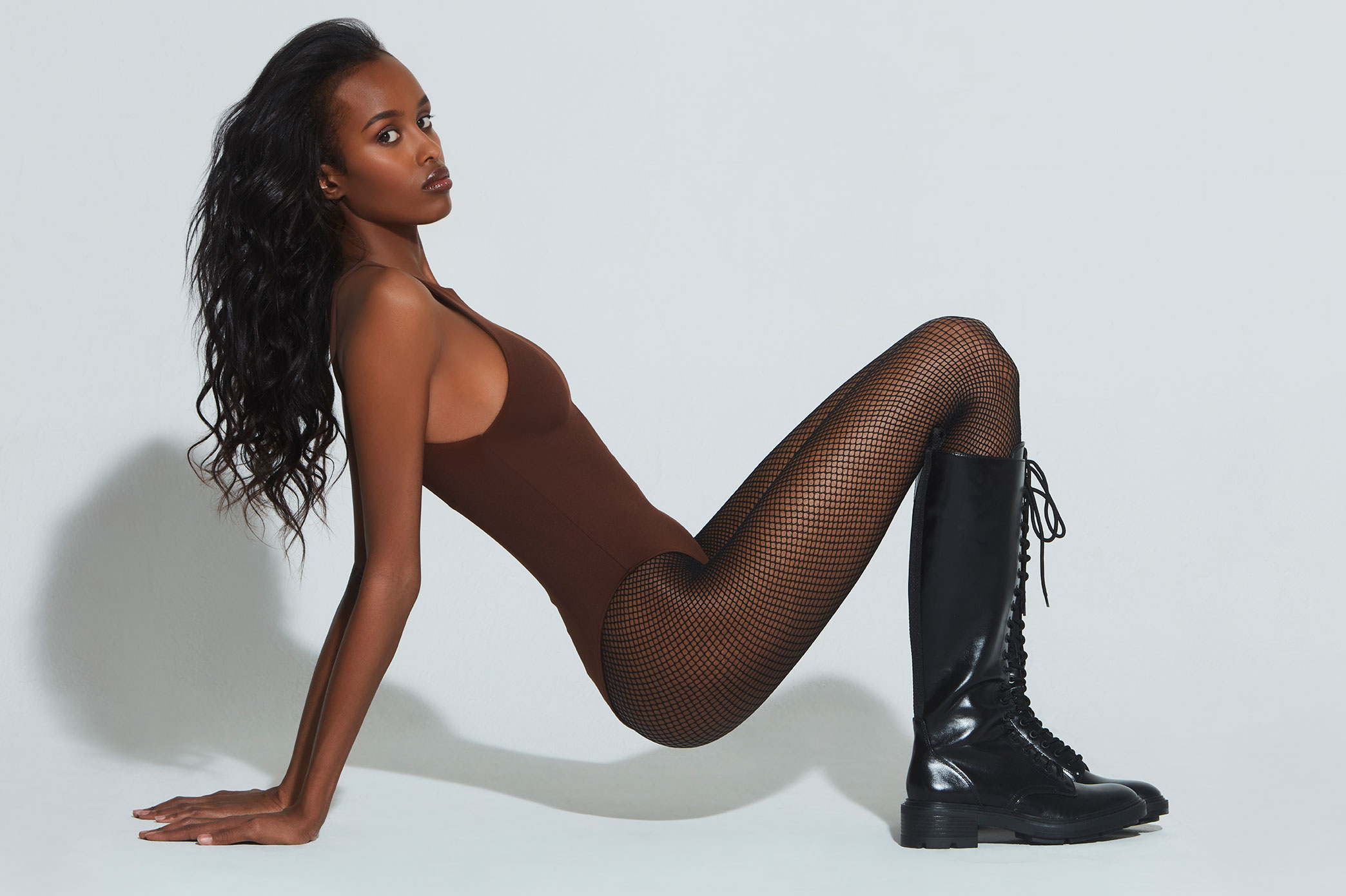 Nasir, One New York, looks amazing in this brown bodysuit matching the richness of her skin. Killer boots and fishnet stockings complete the look. Fashion stylist Brit Lovoi. Hair, makeup, Mua, beauty Veronika Robova