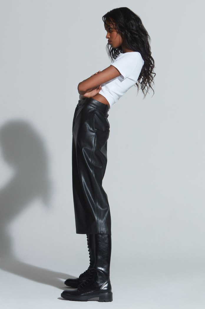 Nasri One New York wears leather pants and white cropped tee with knee-high boots. Loose natural hair and makeup by artist Veronika Robova. fashion stylist Brit Lovoi.
