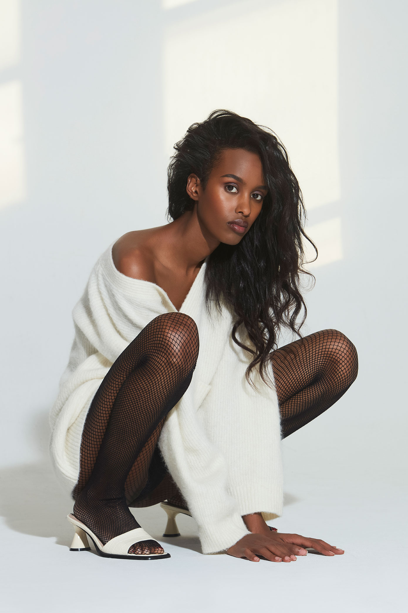 A mix of natural light and studio lighting. Nasri with an oversized cashmere sweater off her shoulder. White mules and fishnet stockings. Great look by Brit Lovoi.