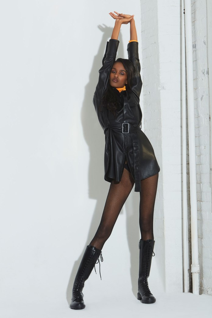 Nasri posing in the corner of the studio wearing a black leather coat, orange turtleneck, fishnet stockings and knee-high lace up boots. Great look by fashion editor stylist Brit Lovoi. Photographed in my New York studio.